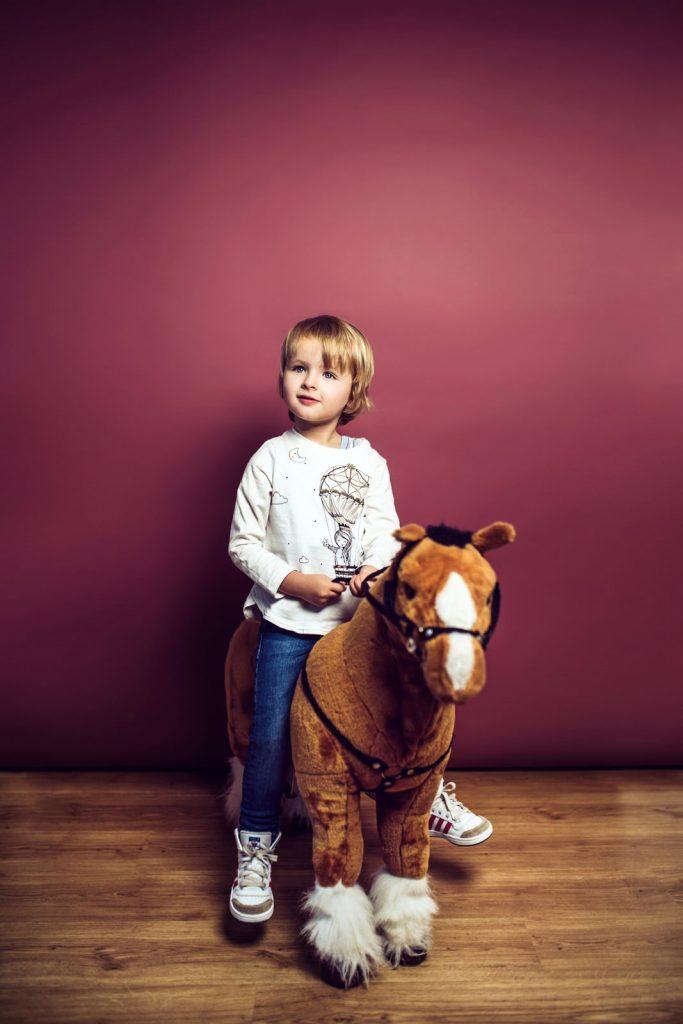 Kind sitzt beim Kinderfotoshooting auf ihrem grossen Kuscheltierpferd.