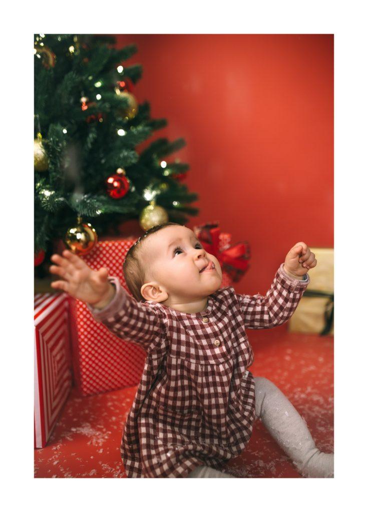 Babybilder zu Weihnachten. Mädchen im roten Kleid sitzt vor dem geschmückten Weihnachtsbaum.