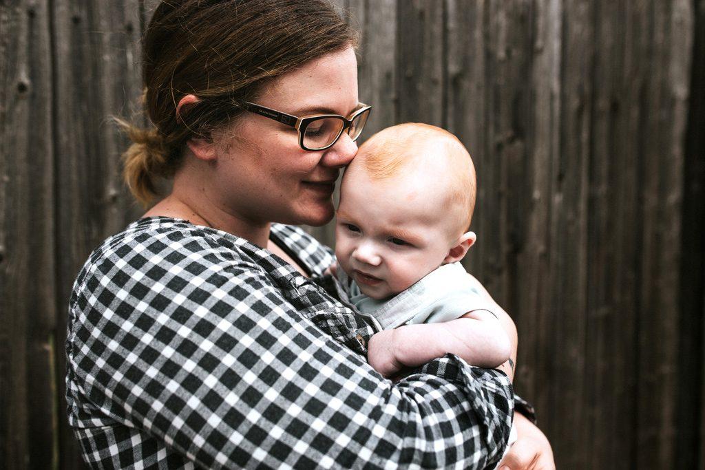 Fotostudio Thomas hat Bilder vor Holzwand in Mutterstadt gemacht. Von Frau mit Baby.